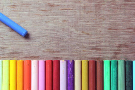 lined up: Crayons lined up in rainbow isolated on wood  Stock Photo