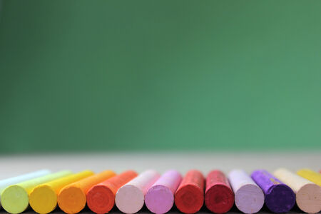 lined up: Crayons lined up in rainbow isolated on green