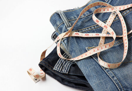 decreasing in size: jeans con nastro di misura, isolato su sfondo bianco