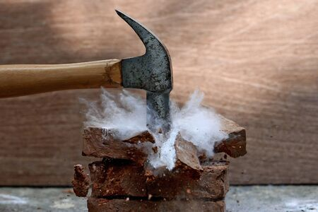 smashing a stone with a hammer.