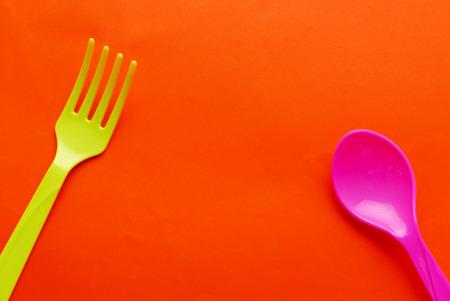 many babies: Colorful plastic spoon isolated on orange background.