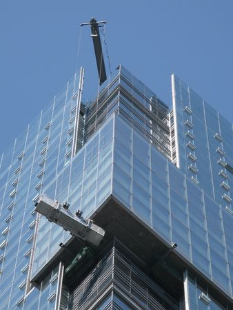 Window cleaners cleaning the glass facade of a modern tower at a great height