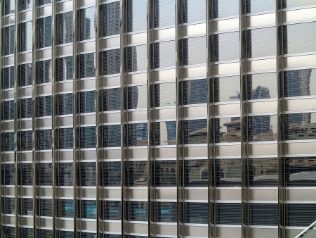frontage: Glass facade of an office building in Dubai, which reflects other buildings