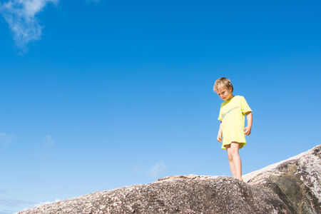A blond boy in a yellow t-shirt is standing on a rock in front of blue sky  photo