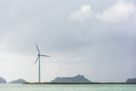 electricity prices: Wind turbine on a coastline at the sea in front of a cloudy sky Stock Photo