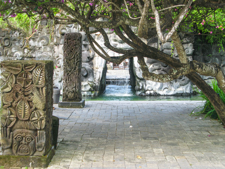 Detail of a pool on Bali with a small cave with waterfall and religious symbols.