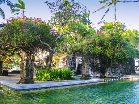 Pool on Bali with a small decorated cave of stone. Stock Photo
