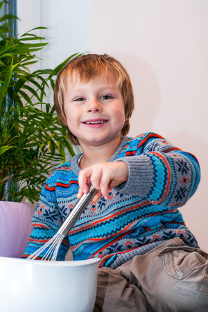 Blond happy boy stirring a cake batter. Stock Photo