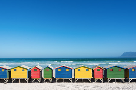 colorful sky: Colorful bathhouses at Muizenberg, Cape Town, South Africa, standing in a row. Stock Photo