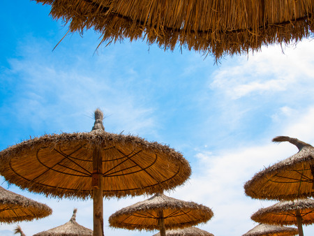 Tops of brown straw parasols against blue sky with clouds. Stock Photo