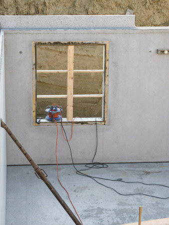 Construction of a basement with a concrete wall with recess for a cellar window.