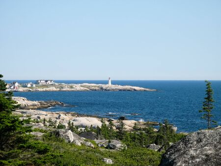 Overlooking a bay with the lighthouse at Peggys Cove, Nova Scotia, Canada. Stock Photo