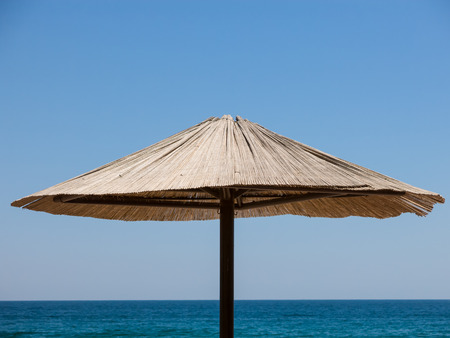 Upper part of a single sunshade made of straw against blue sky and sea.