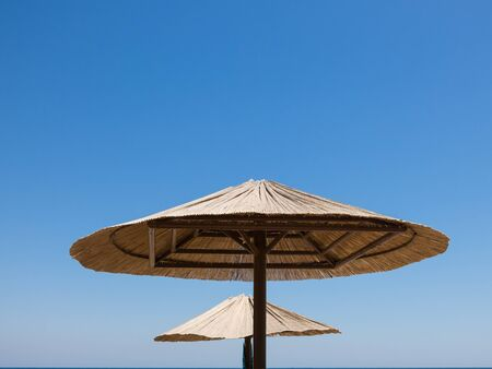 Upper parts of two sunshades made of straw against blue sky and sea. Stock Photo
