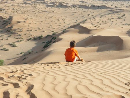 Rear view of a caucasian boy sitting on a sand dune and observing wild camels. Stock Photo