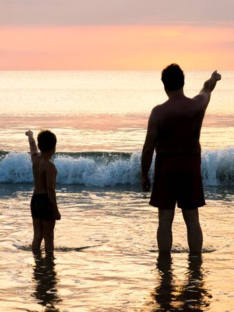 Silhouette of father and son in front of evening sky by the sea pointing in the distance.