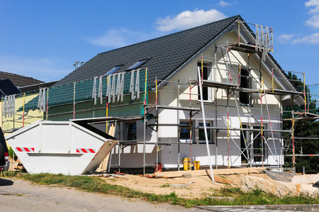 scaffold: Shell of a detached house with scaffold and container Stock Photo