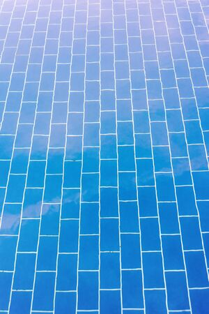 Blue tiled floor of a pool under clear water, in which the sky is reflected Stock Photo