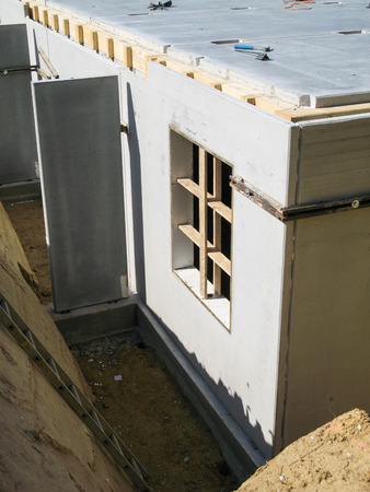 prefabricated house: Construction of a basement with a concrete wall with recess for a cellar window Stock Photo