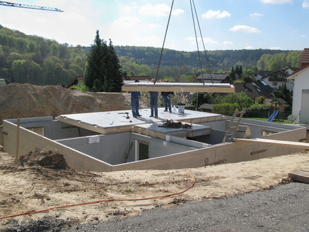 prefabricated house: Three construction workers put a hanging base plate to a finished basement