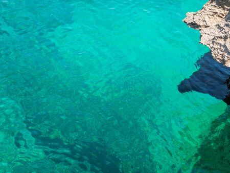Abstract image of clear turquoise sea water, with a rock aside. Stock Photo