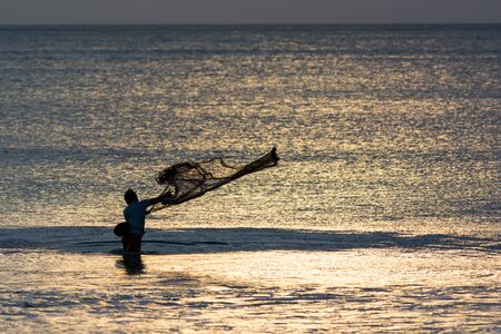 Fisherman standing in water throws his net in backlight.