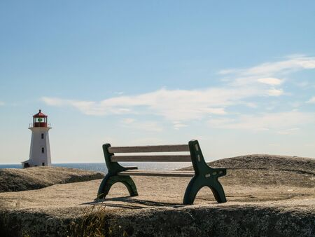 Bench with lighthouse at Peggys Cove, Nova Scotia with View onto the sea.