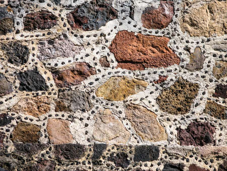 Detail of a stonewall which is made of different rough stones.
