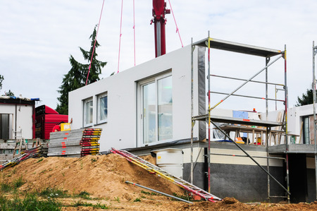housebuilding: Mounting a house wall on a prefabricated house.