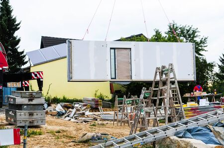 Construction of a prefabricated house with a wall hanging from a crane.