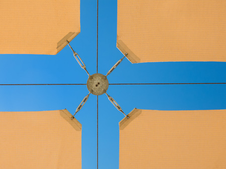 spanned: Detail of a sandy sunshade against a blue cloudless sky.