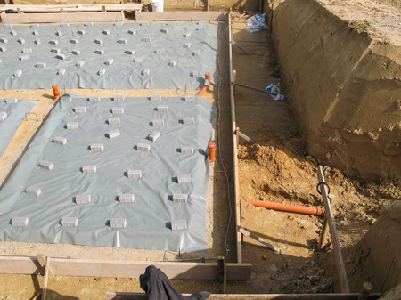 site preparation: Preparing a concrete base in an excavation for a house