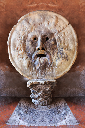 The Mouth of Truth (La Bocca della Verita) carved from Pavonazzo marble, in the portico of the church of Santa Maria in Cosmedin in Rome, Italy