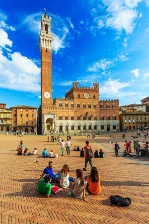 siena italy: SIENA, ITALY - September 30, 2014: tourists enjoy Piazza del Campo square in Siena, Italy. Editorial