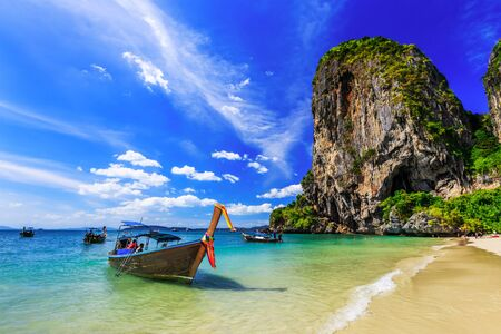 aonang: Thailand, Krabi. Long tail boat on tropical beach with limestone rock. Stock Photo