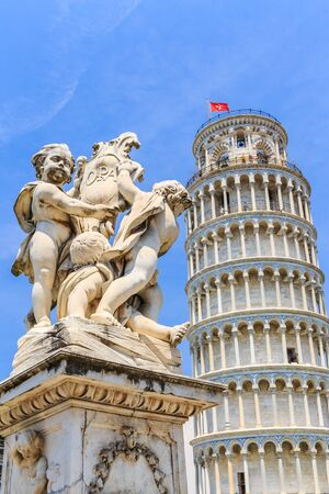 Pisa, Tuscany, Italy. Marble statue in front of the Leaning Tower of Pisa in Piazza dei Miracoli (Square of Miracles).