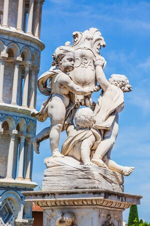 Cupid statue and the Leaning Tower of Pisa in Piazza dei Miracoli (Square of Miracles),  Italy.