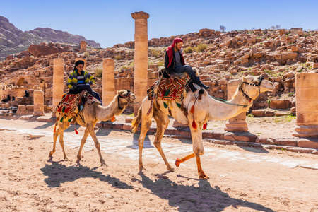 Petra, Jordan - March 4, 2020: Camel riders at the Great Temple of the Nabatean Kingdom.