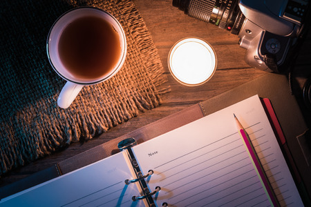 single story: Diary open with pencil near the burning candle on table. Memories of life or travel concept  Top view photo selection focus to a pencil.
