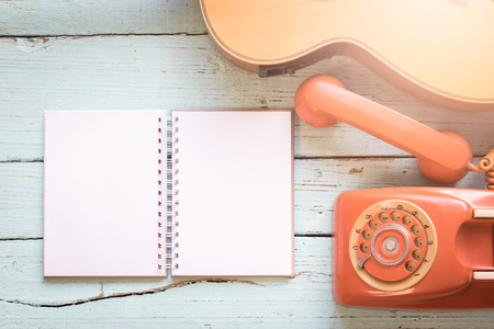 blanks: The diary blanks with retro telephone and acoustic guitar on the wooden table of music composer for musical notes.