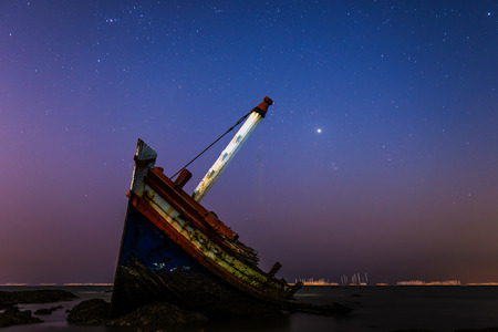 Shipwreck or wrecked boat on beach at night time.