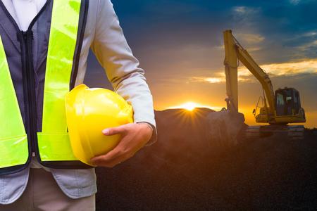 supervisores: Ingeniero o el oficial de seguridad que sostiene el sombrero duro con la máquina excavadora en el sitio de construcción en el tiempo de suspensión es de fondo.