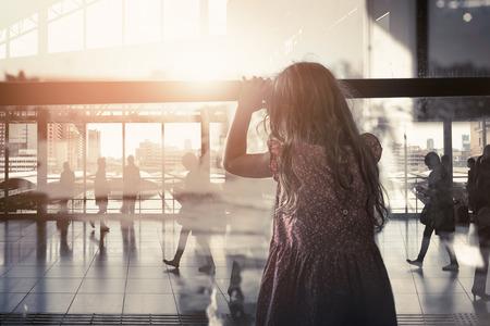 Het kleine meisje kijkt door het raam alleen afscheidsgevoelens. Donkere toon kleur verdriet emoties concept. Stockfoto