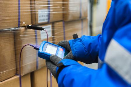 Hand des Arbeiters mit Thermometer zur Temperaturmessung in den Warenkisten mit Fertiggerichten nach dem Import in den Kühlraum oder Lager für den Temperaturraum