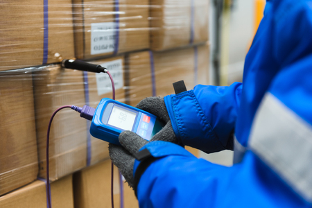 Hand of worker using thermometer to temperature measurement in the goods boxes with ready meals after import in the cold room or warehouse for keep temperature room Foto de archivo