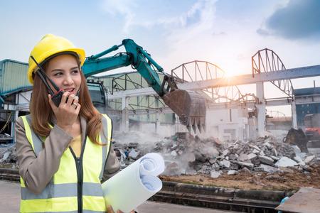 Mujer ingeniera hablando con un walkie-talkie para comunicarse con el proveedor y sosteniendo papel de dibujo en el proyecto de construcción para planificación y gestión.