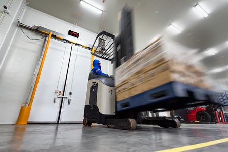 Operaio Carrello elevatore con operatore a bordo utilizzato per sollevare e movimentare lo stock di prodotti di piatti pronti in cella frigorifera o cella freezer. Archivio Fotografico