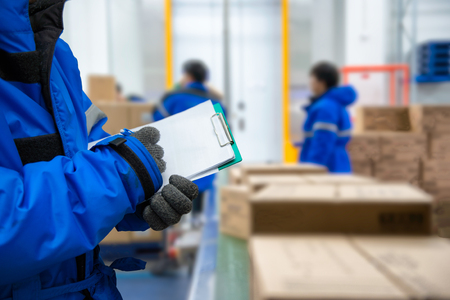 Closeup shooting hand of worker with clipboard checking goods in freezing room or warehouse Фото со стока