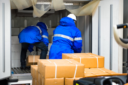 Manual worker working with package boxes for transport by pickup at gates for goods in loading area from warehouse to be processed export to customer Imagens
