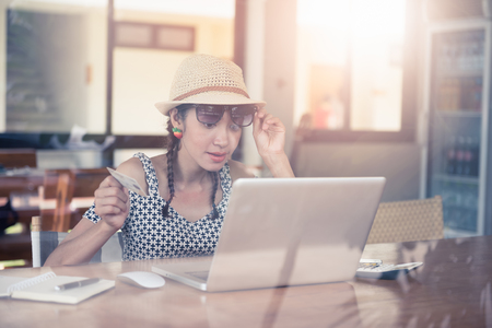 Happening of asian woman doing online shopping lying in the coffee shop. Stock Photo